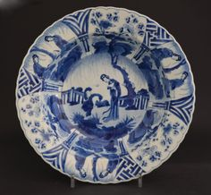 A Kangxi Porcelain Deep Dish c.1700. The Blue and White Porcelain Dish is Painted with a `Long Eliza` (Lange Lyzen) within a Garden Landscape Next to a Dancing Boy (referred to as a `Jumping Boy` on English porcelain).