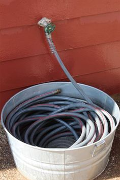 20 Clever DIY Storage Solutions: Keep your hose neatly coiled in a tin basket.