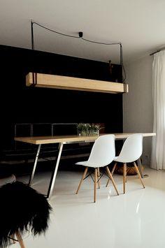 Une suspension massive qui vient équilibrer l'espace, en réponse au plateau de cette table et aux pieds de ces chaises Eames.