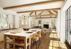 Open space farmhouse kitchen design. Cream cabinets, light wood floors, island is different from cabinets - wood with light stone top