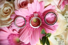 Solitaire engagement ring and white gold wedding bands and the brides pink and white bouquet