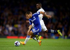 Eden Hazard of Chelsea is tackled by Medo Kamara of Bolton during the Captial One Cup Third Round match between Chelsea and Bolton Wanderers at Stamford Bridge on September 24, 2014 in London, England