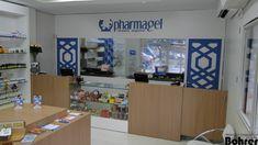 Loja em MDF branco com formica liquida azul tendo balcões em MDF madeirado.
