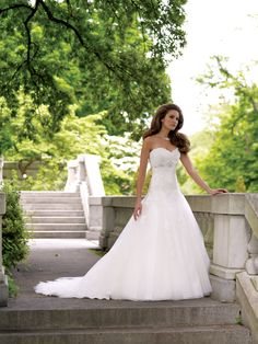 Strapless tulle and lace full A-line gown with sweetheart neckline, delicate lace bodice features intricate hand-beaded jeweled motif at empire waist, dropped waistline, full tulle skirt with matching lace appliqués, chapel length train, detachable spaghetti and halter straps included. Sizes: 0 – 20