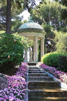A gorgeous classical gazebo with a Grecian style statue inside makes a wonderful focal point for the structure of the steps & the trees beyond.