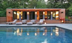 This pool house in Connecticut was fashioned from two shipping containers, bedecked in well-lit cedar, which contrasts beautifully with the blue of the water.