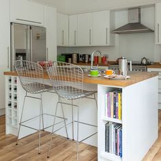 White kitchen with breakfast bar  The island in this modern and minimalistic kitchen not only doubles as a breakfast bar, but also has plenty of storage for bottles of wine and recipe books. An oak-effect floor and wooden worktops give the kitchen an earthy look.