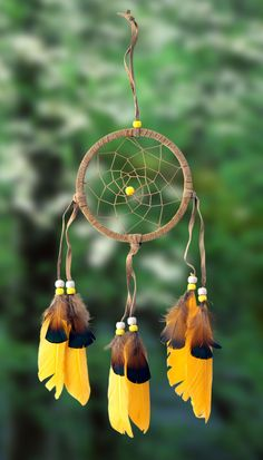 "4-1/2"" diameter ring wrapped in tan leather and adorned with leather straps and yellow feathers with brown & black tops. Accented with yellow and white beads. Size: 4-1/2"" x 16"". Comes wrapped individ"