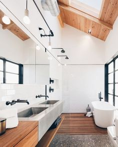 A skylight illuminates the neutral master bathroom letting bathers contemplate the clouds. The faucets and tub are by @brizofaucet and the sinks are @slabhaus