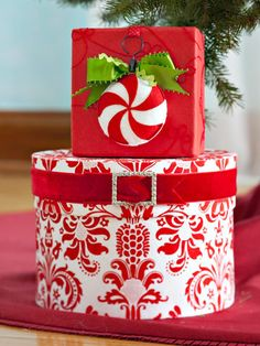 Peppermint Swirls Ornament ~~ Well-dressed gifts can be an integral part of the decorating scheme. Here, a peppermint ornament, cleverly hung with a curtain clip, dresses up a simple box. The paper-covered hatbox is accented with a velvet ribbon belted with a rhinestone buckle.