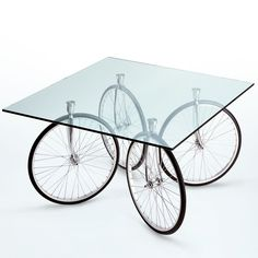 "An everyday object whose sculptural and technical beauty cannot be overlooked by the discriminating eye. This table from designer Gae Aulenti showcases four bicycle tire legs beneath a float ground-glass top. Float ground-glass top (0.6"" thick). Rotating wheels fixed to the top by four stainless steel plates. Chromium-plated brackets. All-rubber wheels. Material(s): Glass, stainless steel and rubber H 28.7"" W 47.2"" D 47.2"" FontanaArte was founded by architect Gio Ponti in 1932. A leader in…"