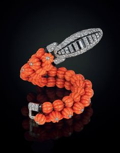 An Art Deco coral, diamond and onyx bracelet, by Cartier.   Designed as three rows of carved coral beads, the top row enhanced by collet-set circular-cut diamonds, joined by a circular and baguette-cut diamond clasp, with onyx detail, circa 1930  French assay marks for platinum. Signed Cartier, Paris, with maker's mark,