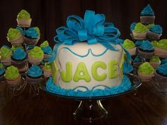 Baby boy shower cake. Three layer fondant covered 8 inch round vanilla cake with buttercream frosting. Two cupcake towers with chocolate and vanilla cupcakes topped with buttercream frosting.