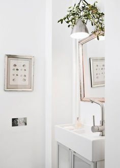 Small powder room. Narrow pedestal sink makes for a unique solution. A monochromatic color scheme creates the illusion of more space.