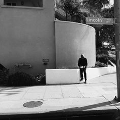 On Lincoln Blvd in Venice, a man sits in front of an apartment building with a newspaper. @americanobscura for @streetvogs