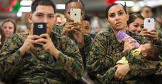 20151226 - Soldados filmam - e até dão mamadeira para bebê - o discurso do presidente Barack Obama durante evento para agradecer os serviços de militares e suas famílias em base do Havaí.  PICTURE: Evan Vucci/AP