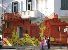 A family stands by a wall of street art in Buenos Aires.  [Nancy Wigston photo]