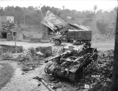 In a village left in ruins, a GMC truck passes behind the German medium tank PzKpfw IV Ausf. J of the German 2. Panzer-Division, destroyed by soldiers of the 35th U.S. Infantry Division, August 2, 1944. Looks like knocked out in airstrike or by heavy artillery barrage.