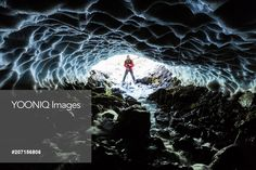 Yooniq images - Caucasian hiker viewing stream from entrance of ice cave
