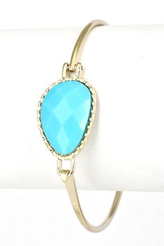 """This designer inspired bracelet is the talk of the town! The turquoise stone looks impeccable! We are loving this bracelet on its own or paired with a watch or more bangles. Acrylic jewel bracelet. Hook closure. Diameter: 2 3/8."""""""