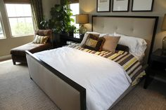 This bedroom features large modern bed frame atop faux-stone carpetting. Burnt brown chaise lounge sits in the corner.