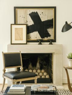 This is such a brilliant mantle set up! The perfectly proportioned, contemporary artwork hung on the wall above the fireplace, paired with the smaller piece, leaning against it is an ideal use of space. The small accessories on the right side of the mantle don't compete with the artwork, but compliment the dark tones of the custom frame mouldings. A winner!