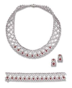 A SUITE OF RUBY AND DIAMOND JEWELRY, BY TIFFANY & CO. Comprising a necklace, the wide flexible openwork band composed of a series of circular-cut diamond links, with diamond collet detail, the front enhanced by pear-shaped ruby accents; a bracelet and a pair of ear clips en suite, mounted in platinum and 18k gold, necklace 15¾ ins., bracelet 6½ ins., necklace in a Tiffany & Co. black suede case Signed Tiffany & Co., France