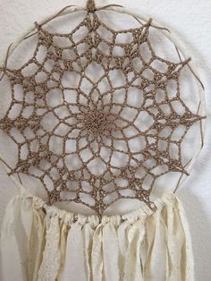 I made this dream catcher with a crochet center doily. Long fabric strips. 10 ring. Longest Strips 21. The dream catcher measures 31.