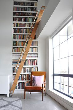 White walls, grey floor, patterned rug, orange chair with pink pillow, white bookshelves, and wooden ladder