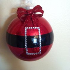 Cute Santa ornament. I used pledge floor cleaner on the inside of a glass ornament; drained out the remaining pledge after coating the inside of the ornament. I then funneled fine glitter into the ornament and shook it until the entire bulb was coated. To get a straight line, I taped of the ornament then painted between the tape with black acrylic paint. Once the paint dried, I painted over it with a clear nail polish top coat. To finish it off, I used stick on rhinestones to make the belt buckle.