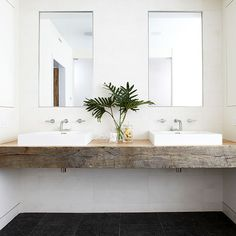 Simple white vessel sinks are the perfect complement to many surfaces. In this bathroom, a floating piece of salvaged wood creates a unique double vanity./