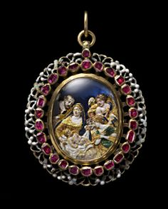 Gold and silver oval locket, the front with an outer border of black and white openwork ornament surrounding a line of table-cut rubies enclosing a glass covered cut-out gold enamelled scene of the Nativity, with two angels in the stable adoring the infant Jesus watched by his mother, the Virgin Mary and by St. Joseph set against a blue foil ground...