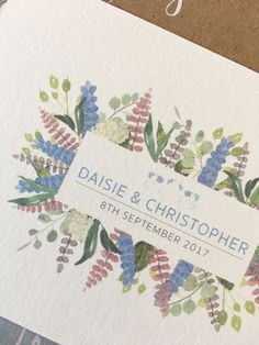 Watercolour wildflowers and illustrated cows made up the logo for Daisie and Christopher's farm inspired rustic wedding invitations