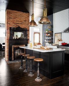 An industrial kitchen with black painted ceiling, exposed brick fireplace, wood kitchen stools, and large pendant lights Country Kitchen, New Kitchen, Kitchen Dining, Kitchen Decor, Kitchen Stools, Bar Stools, Island Stools, Kitchen Modern, Rustic Kitchen