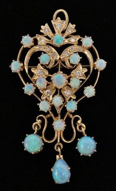 """Early 20th century. Ladies necklace pendant of heart form with sixteen opals on diamond accented heart body with three larger opals (one teardrop) dangling below. Pendant with pin hook on back and marked """"14K"""" on necklace hoop. Total weight approximately 19.3 grams."""