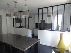 La cuisine est séparée par une baie vitrée d'atelier, créée pour donner de la lumière. Elle est ouverte en partie sur le salon.