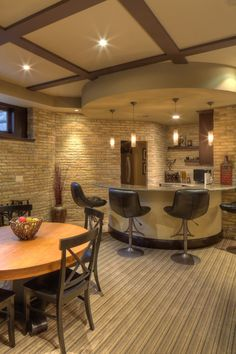 Very cool basement design. A curved counter, a circular soffit andpendant lighting define a bar area in the corner.And still have room for maybe a card game?