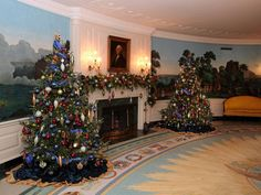 A White House Christmas 2012  The Diplomatic Reception Room fireplace is flanked with trees accented in a red, white, blue and gold color scheme. The mantel features elegant garland and hanging ornaments to continue the theme.