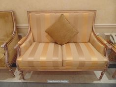 Lot 502 - Italian Neoclassical style antiqued distressed wood and parcel gilt upholstered two seater sofa