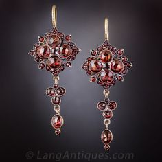 Bohemian Garnet Drop Earrings. Quintessential Bohemian garnet dangling drops by way of late-nineteenth century eastern-Europe - most likely Czechoslovakia. An array of dusky reddish orange garnets glisten and glow from within darkly patinated, gilded metal mounts, measuring 1 3/4 inches long.