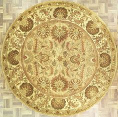 Handmade and tufted circular area rug with leaf and floral designs in camel with beige accents,  8x8. Imported from India with wool. Free Shipping within the US.