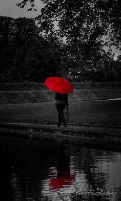 The red umbrella strolls around the park lake...