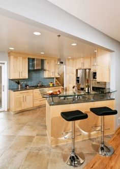 Maple cabinets with stone floors. Lighten the countertops and backsplash.