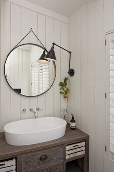 Cottage powder room with gray washed vanity accented with oil rubbed bronze cup pull hardware and rustic crate drawers topped with an oval vessel sink paired with wall mount faucet situated below captain's mirror lit by an oil rubbed bronze adjustable wall sconce over tongue and groove planked walls.