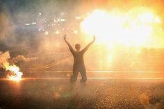 This woman in Ferguson, Missouri, demonstrating on her knees amid a cloud of tear gas in 2014. | 32 Of The Most Badass Moments In History