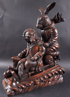 A BLACK FOREST DESIGN CARVED WOOD BOX as a rabbit and a fox on a sleigh. 19ins high.