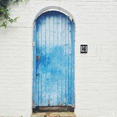 white bricks + a weathered azure door.