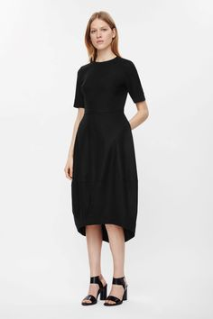 This dress is made from smooth wool-mix with a cocoon shape, graduated skirt. Coming in at the waist, it has a round neckline, short sleeves and a hidden back zip.