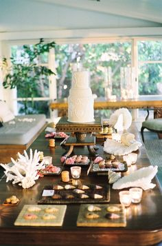 An array of desserts were displayed near a wedding cake on a wooden table topped with seashells and coral. #DessertTable Photography by: Steve Steinhardt. Read More: https://www.insideweddings.com/weddings/tropical-romantic-destination-wedding-in-hawaii/397/