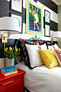 Bold, colorful girl's bedroom  ||  black and white stripes  ||  glossy red nightstands  ||  swing arm wall sconces  ||  Crane and Canopy Linden bedding  ||  vintage peacock headboard